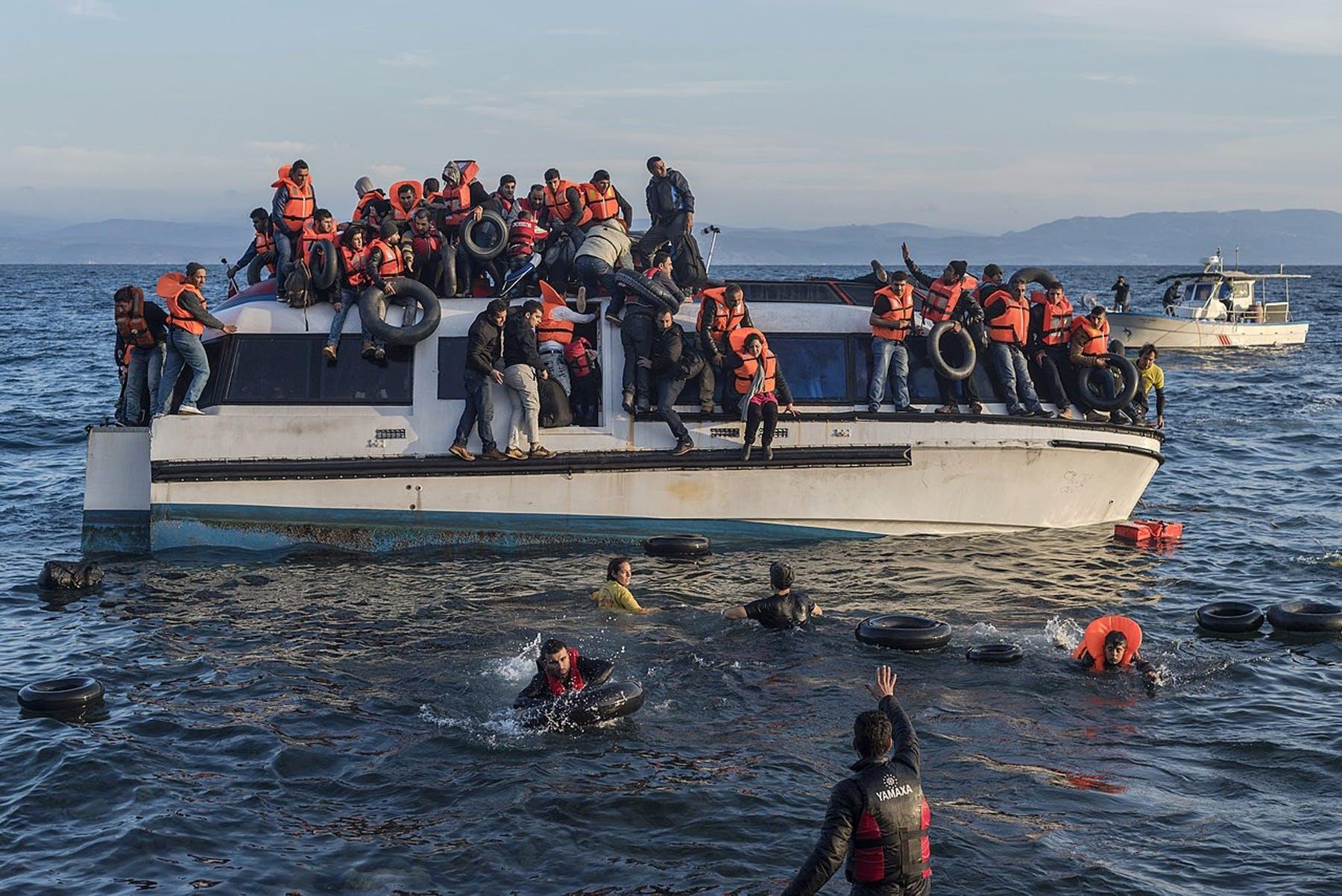 Refugiados sirios e iraquíes tratan de desembarcar en las aguas costeras de Lesbos en Grecia, después de haber cruzado desde Turquía.